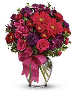 Red carnations, pink roses, purple carnations and more fill a clear vase