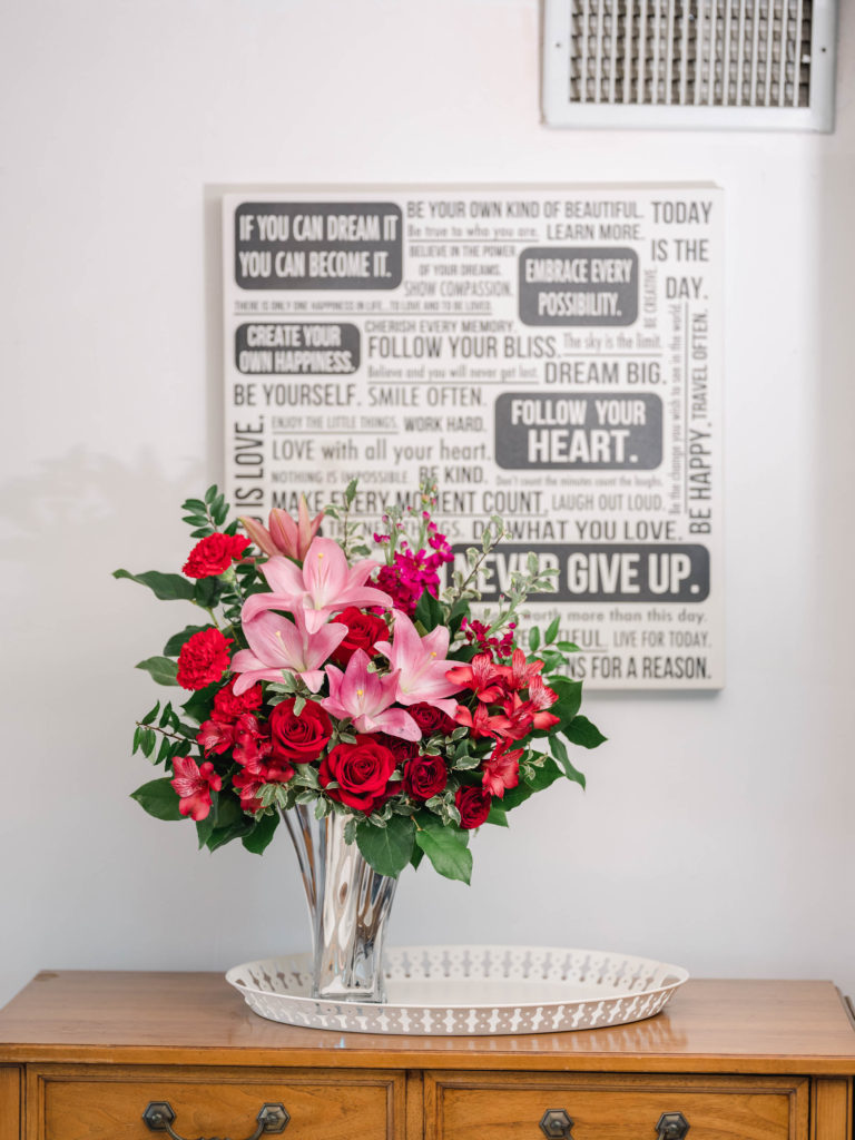 Red roses, pink lilies, and greenery fill a silver vase on a dresser