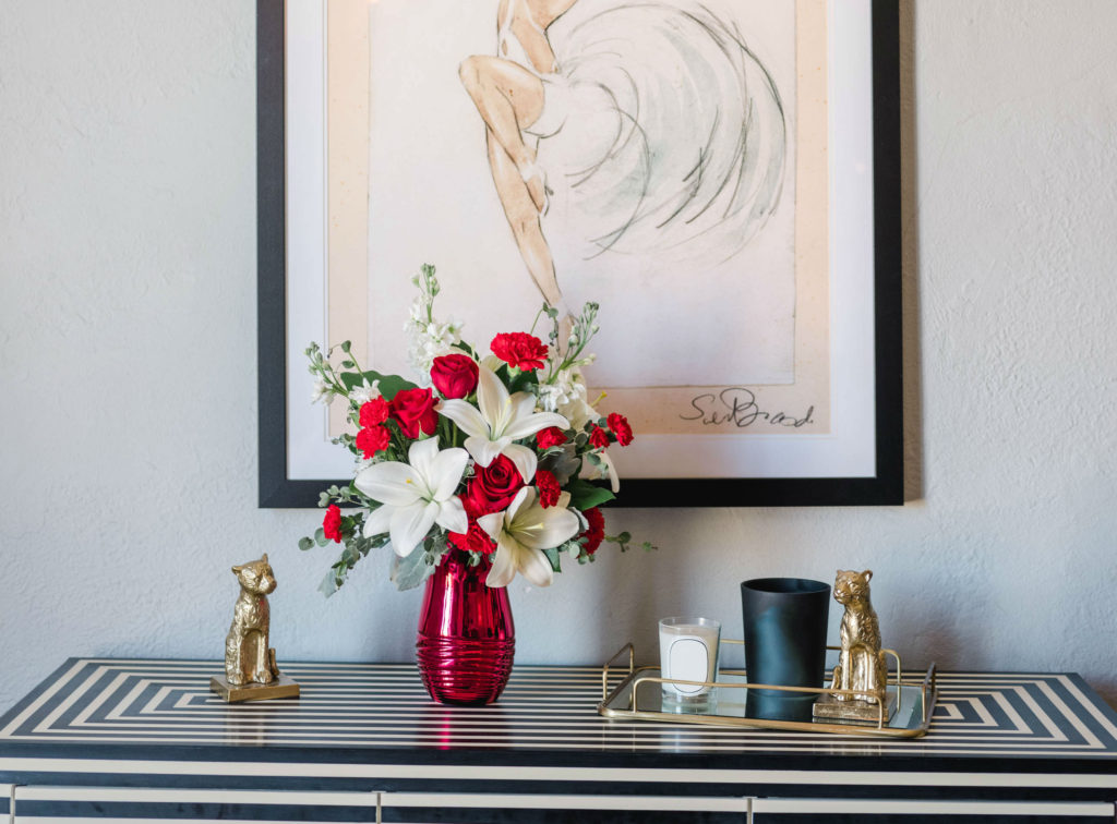 White lilies and red roses in a red vase on a black and white dresser