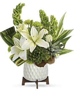 Green succulents and white lilies fill a white container