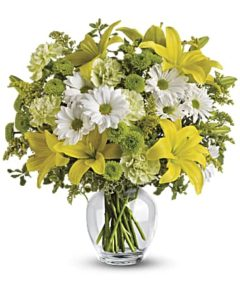 Yellow lilies and daisies fill a clear vase