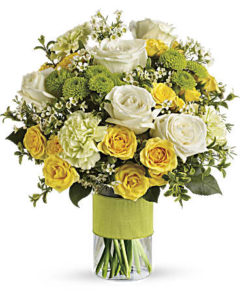 Yellow roses and while roses and carnations fill a clear vase with a ribbon tied around it