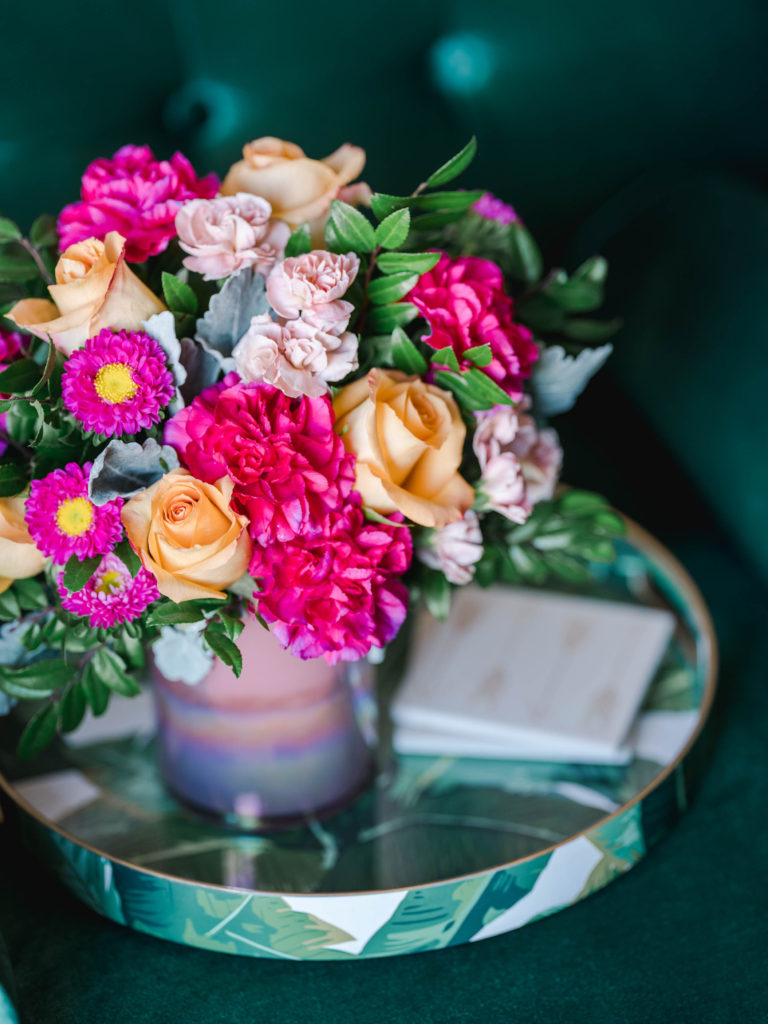 Pink and peach flowers pop against a pink vase on a side table