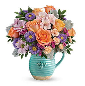 Orange roses, purple carnations, and more fill a blue pitcher vase