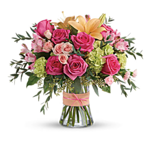Hot pink roses, orange lilies, and more fill a clear vase