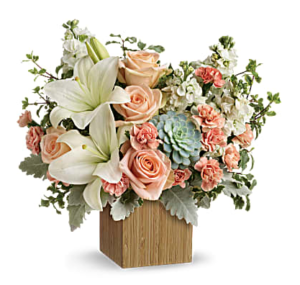 Peach roses, white lilies, and succulents fill a bamboo container