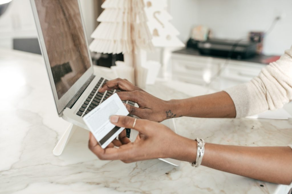 lady with credit card in hand by a computer