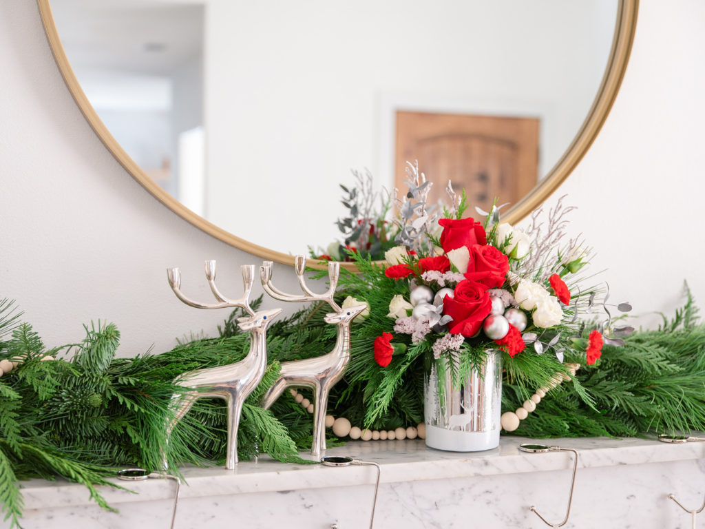red flowers in silver vase on mantel with garland