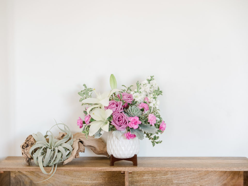 Purple roses and white lilies fill a white vase on mantle