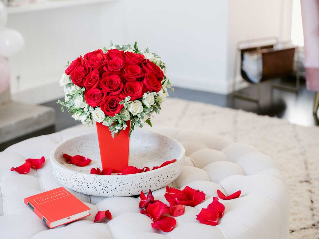 Red roses in a red vase on a bed with a book