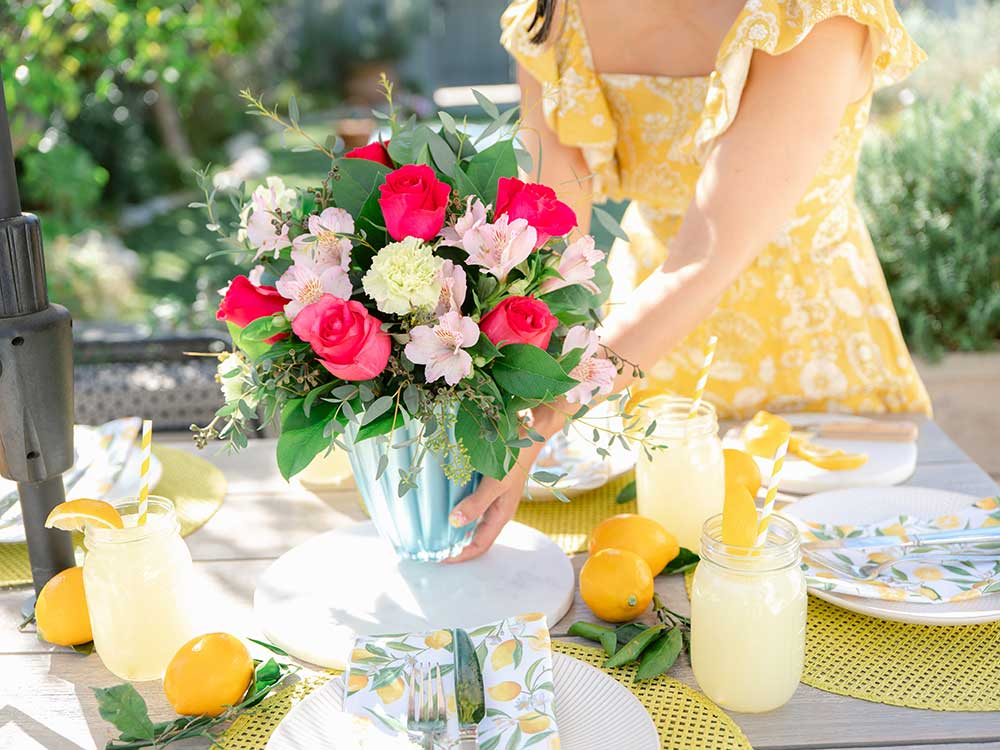 Pink and white flowers in a blue vase on a table with lemonade