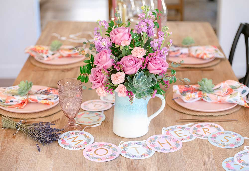 Pink and purple flowers fill a blue pitcher vase on a table