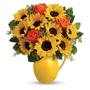 Sunflowers and orange roses fill a yellow pitcher