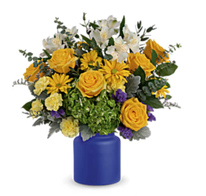 Yellow, green, and white flowers fill a blue vase