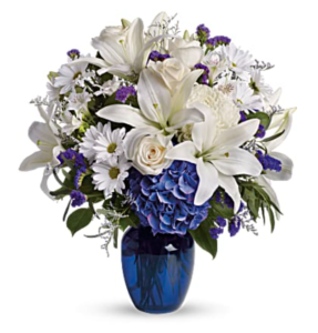 White lilies and blue hydrangeas fill a blue vase